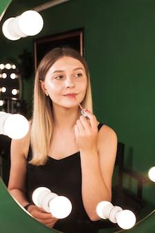 Fille la maquillant dans une chambre verte
