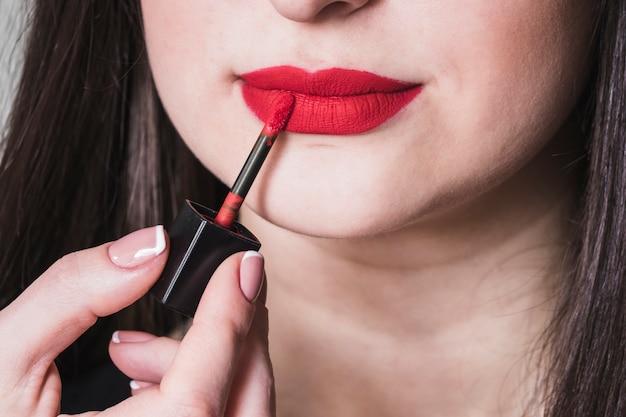 Fille maquillant les lèvres