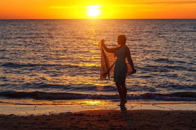 Fille marchant au bord de la mer au concept de vacances coucher de soleil
