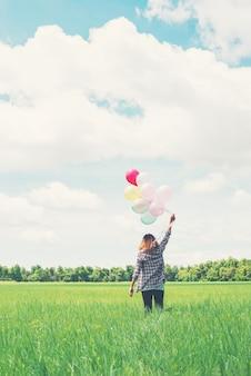 Fille marchant avec des ballons dans la prairie