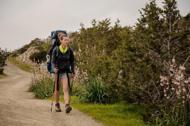 Fille marchant sur le chemin vert avec sac à dos et stiks de randonnée