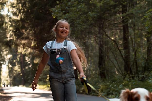 Fille marchant et courant avec un chien en laisse flexible dans le parc de la ville en été