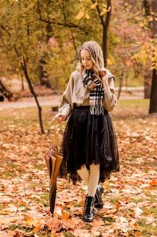 Fille marchant avec un parapluie dans le parc en automne