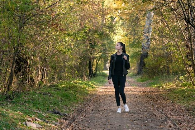 Fille marche dans le parc en automne. belle jeune femme en vêtements noirs dans la forêt. ruelle, promenade.