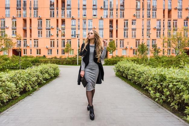Une fille marche dans le parc sur un fond de construction