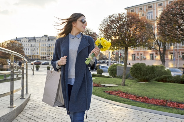 Fille marche dans la ville, jeune femme avec bouquet de fleurs et sac à provisions