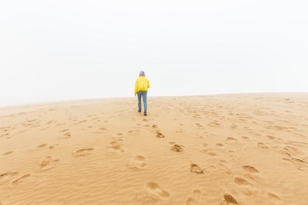 La fille marche sur une dune de sable. barkhan sarykum, - russie, daghestan, mars 2020. dune, sand mountain-barkhan sarykum.
