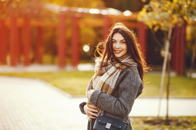 Fille marche. femme dans un manteau. brunette avec un foulard.