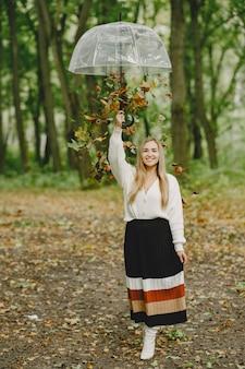 Fille marche. femme dans un pull blanc. blonde avec parapluie. feuilles tombantes.