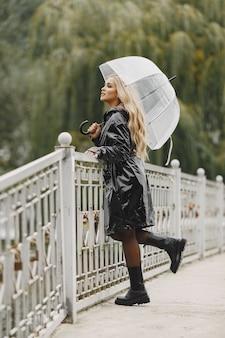 Fille marche. femme en manteau noir. blonde avec un parapluie.