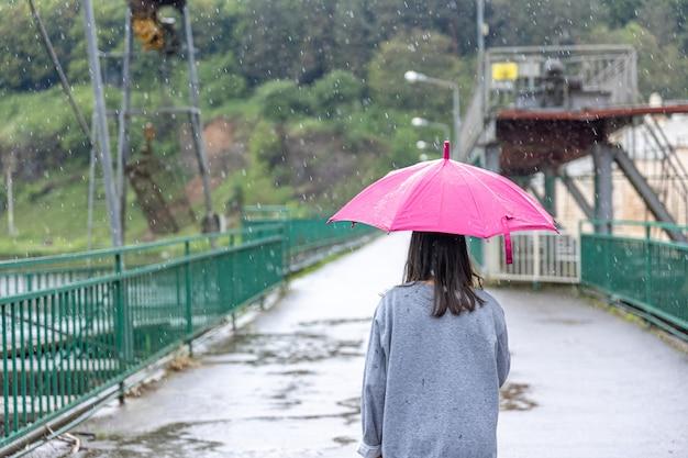 Une fille marche sous un parapluie par temps de pluie sur un pont dans la forêt.