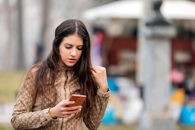 Fille marche et textos sur le téléphone intelligent dans la rue