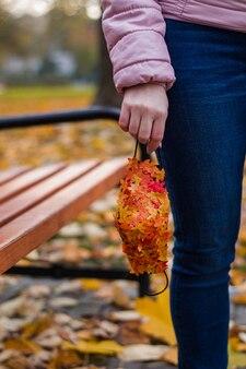 Fille avec masque antiviral avec des feuilles d'automne dans le parc