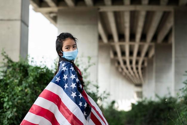 Fille avec masque et drapeau américain coup moyen