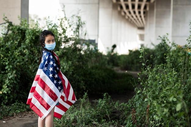 Fille avec masque et drapeau américain