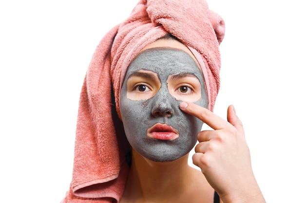 Fille avec masque facial, masque pour femme de peau, fille touche un masque facial au doigt, fille drôle, photo isolée, la fille attend le masque pour la peau