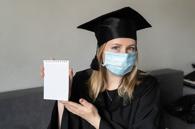 Fille en masque médical avec chapeau de robe de graduation tenant un petit cahier sur fond gris
