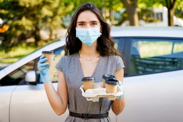 Fille en masque médical et gants tient le plateau de tasses à café jetables
