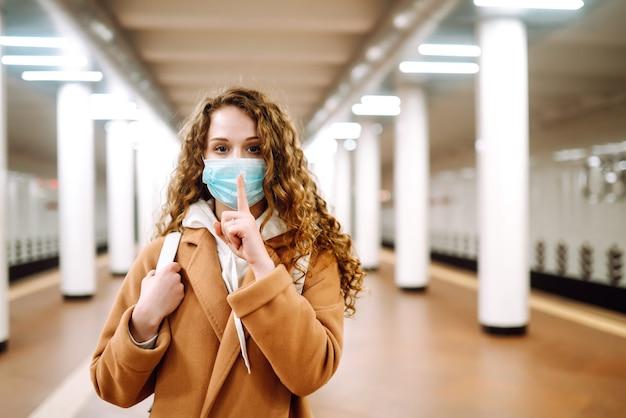 Fille en masque médical stérile protecteur sur son visage montre un geste: chut. silence.