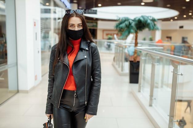 Fille avec un masque noir médical marche le long d'un centre commercial. pandémie de coronavirus.