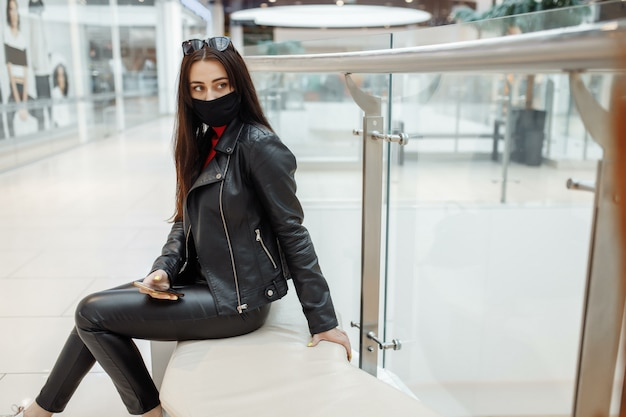 Fille avec masque noir médical et téléphone mobile dans un centre commercial. pandémie de coronavirus. femme avec un masque se tient dans un centre commercial.