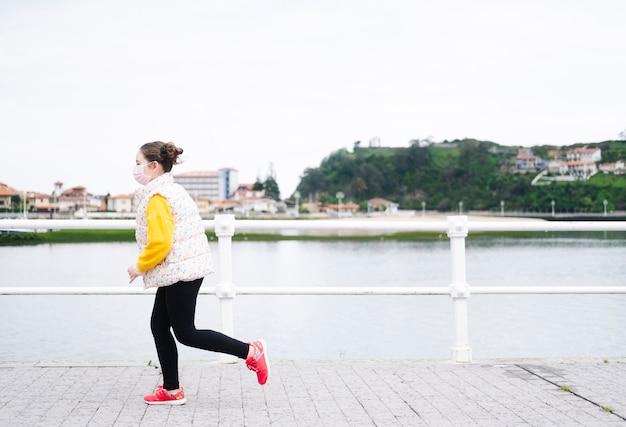 Une fille avec un masque par une promenade dans un pull jaune