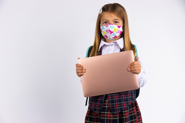 Fille avec un masque personnalisé retournant à l'école après la mise en quarantaine et le verrouillage de covid-19 forme scolaire et ordinateur portable à la main.