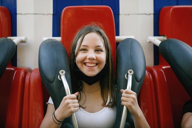 Fille en masque de protection sur carrousel ou attraction dans le parc d'attractions d'été dans la ville