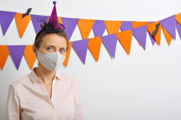 Une fille avec un masque sur son visage et un chapeau de sorcière se penche sur la célébration d'halloween frameon
