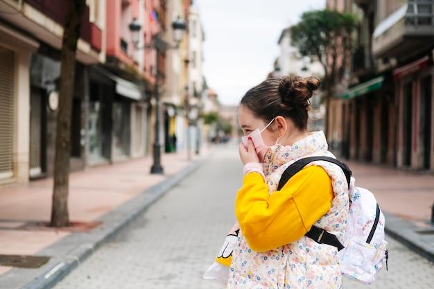Une fille avec un masque sur son visage dans la rue d'une ville
