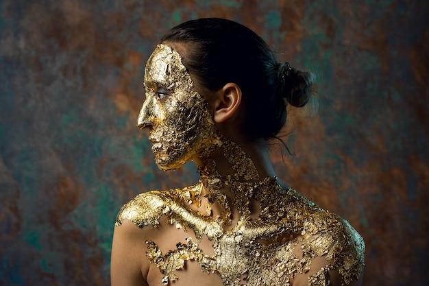 Fille avec un masque sur son visage fait de feuille d'or portrait en studio sombre d'une brune sur un résumé