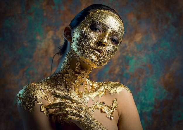 Fille avec un masque sur son visage en feuille d'or portrait en studio sombre d'une brune