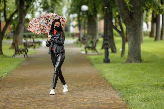 Une fille masquée marche le long de la rue. une fille dans un masque de protection se promène dans le parc avec un parapluie sous la pluie. infection à coronavirus covid-19.