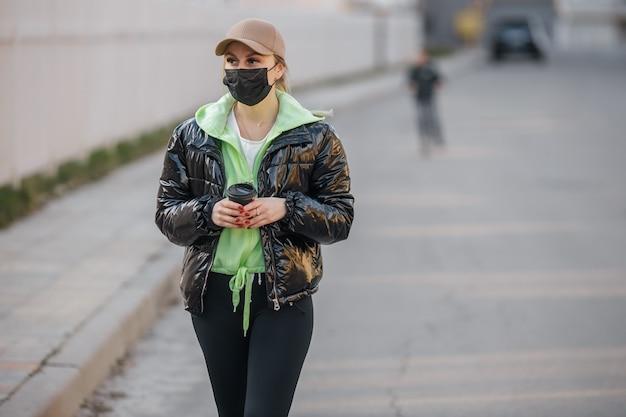 Une fille masquée marche le long de la rue infection à coronavirus covid