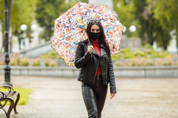 Une fille masquée marche le long de la rue.