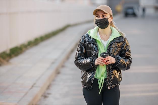 Une fille masquée marche le long de la rue