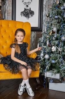 Fille et un matin de noël, un enfant posant contre l'intérieur de l'arbre de noël