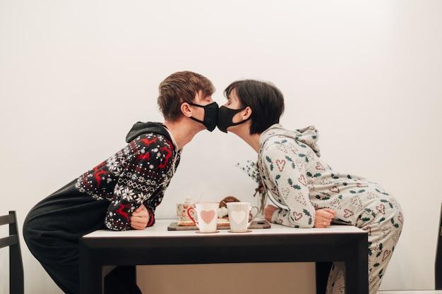Fille et mec s'embrassant dans des masques en quarantaine covid-19.