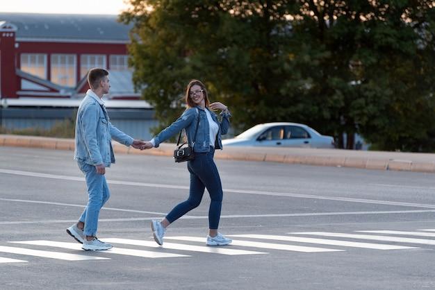 Une fille et un mec traversent la route par la main. suivez-moi.