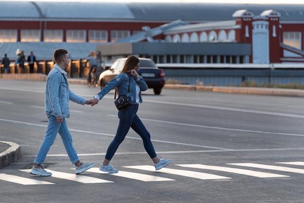 Une fille et un mec traversent la route par la main. toujours ensemble.