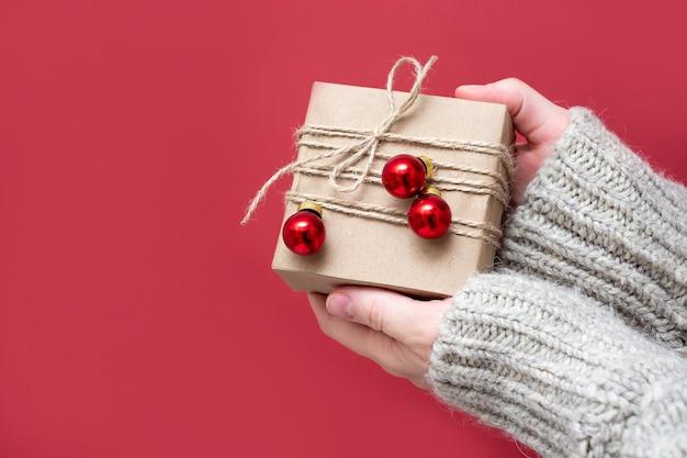 Une fille méconnaissable dans un pull tient un cadeau emballé de ses propres mains sur fond rouge, gros plan. concept de noël, faites des surprises, offrez des cadeaux. fond de nouvel an.