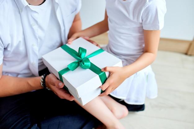 Fille méconnaissable félicitant papa et donnant un cadeau d'anniversaire à la maison.