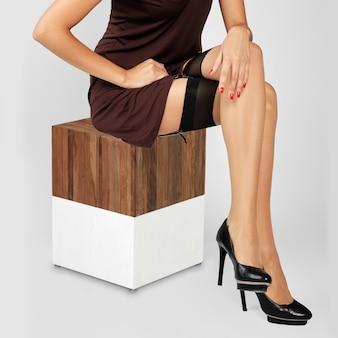 Fille méconnaissable avec de longs cheveux bouclés assis dans une robe courte et des bas avec jarretière