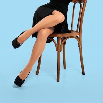 Fille méconnaissable posant sur une chaise en studio
