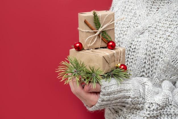 Une fille méconnaissable en pull tient des cadeaux de noël sur fond rouge. coffrets cadeaux faits à la main dans les mains d'une femme. fond de nouvel an avec de beaux cadeaux.