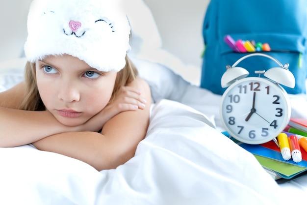 Fille mécontente en masque dort dans son lit avec réveil, sac à dos scolaire, marqueurs, crayons, cahiers