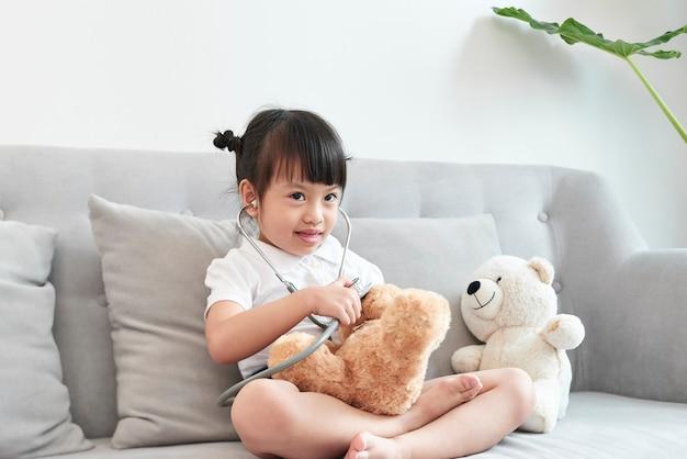 Une fille médecin jouant et soigner un ours à la pédiatrie