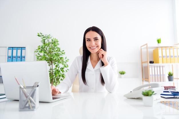 Fille de médecin positif s'asseoir dans le bureau de l'hôpital médical travaille sur ordinateur portable