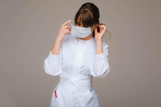 Une fille médecin se tient dans un masque médical, isolé sur un fond gris