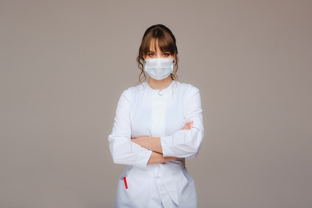 Une fille médecin se tient dans un masque médical, isolé sur un fond gris.